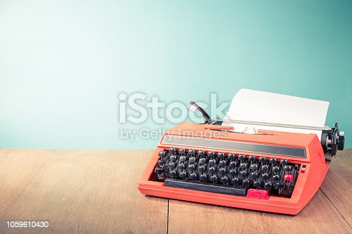 istock Retro old typewriter with paper sheet on wooden table front mint green background. Vintage style filtered photo 1059610430