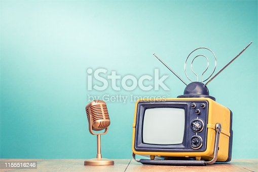 1056306726istockphoto Retro old yellow TV receiver with antenna and golden microphone on wooden table front gradient aquamarine wall background. Vintage instagram style filtered photo 1155516246