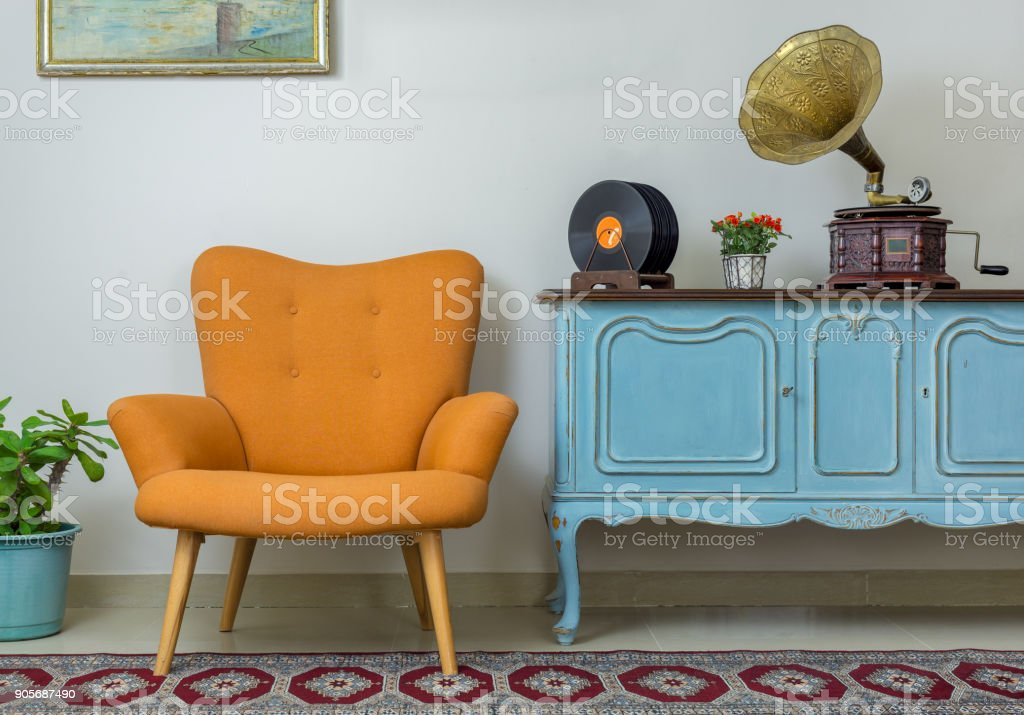 Retro orange armchair, vintage wooden light blue sideboard, old phonograph (gramophone), vinyl records on background of beige wall, tiled porcelain floor, and red carpet stock photo