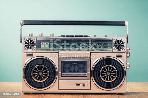 1043737676 istock photo Retro outdated cassette tape recorder from 80s on table front mint green background. Vintage old style filtered photo 1054704806