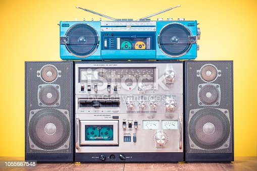 1043737676 istock photo Retro outdated HI FI stereo boombox system and aquamarine radio cassette recorder from 80s front yellow background. Vintage instagram old style filtered photo 1055667548