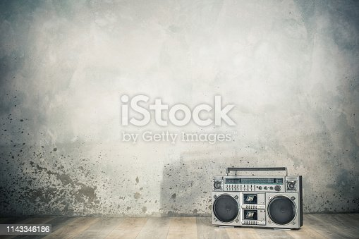1043737676 istock photo Retro outdated portable stereo boombox radio cassette recorder from 80s front concrete wall background with shadow. Vintage old style filtered photo 1143346186