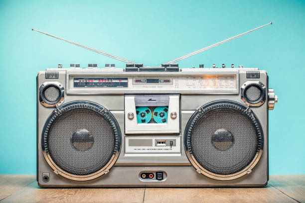 Retro outdated portable stereo boombox radio receiver with cassette recorder from circa late 70s front aquamarine wall background. Listening music concept. Vintage old style filtered photo stock photo