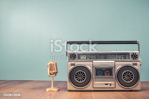 1043737676 istock photo Retro outdated portable stereo boombox radio receiver with cassette recorder from circa 80s and golden mic front mint green wall background. Recording music concept. Vintage old style filtered photo 1043613538