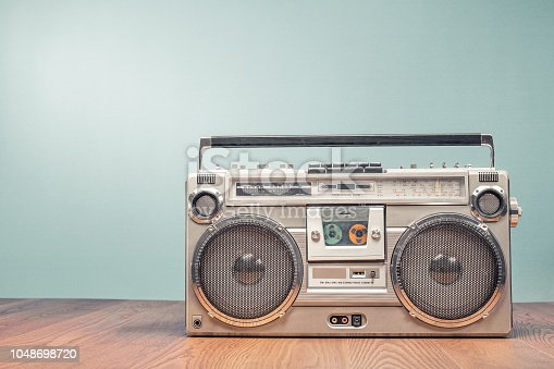 istock Retro outdated portable stereo boombox radio receiver with cassette recorder from circa late 70s front mint green wall background. Listening music concept. Vintage old style filtered photo 1048698720