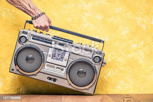 1043737676 istock photo Retro outdated portable stereo boombox radio receiver with cassette recorder from circa 1980s in a strong man's hand front concrete textured yellow wall background. Vintage old style filtered photo 1077389990
