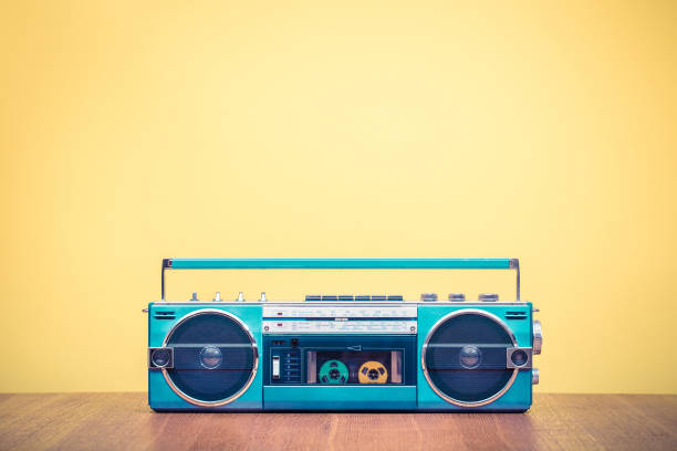 Retro outdated portable stereo mint green radio cassette recorder from 80s front yellow background. Vintage old style filtered photo stock photo