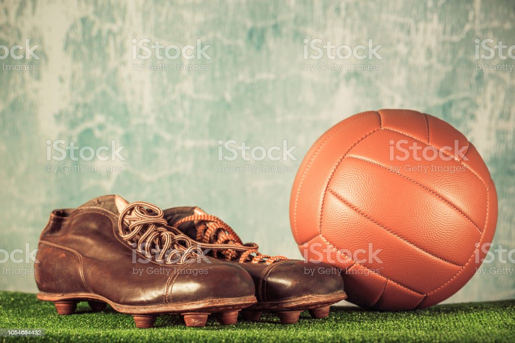 5abf2a51c Retro outdated soccer spike boots and football. Vintage old style filtered  photo - Stock image .
