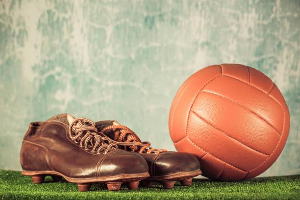 retro-veraltete fußballschuhe spike und fußball. vintage alte stil gefilterten foto - fußball poster stock-fotos und bilder