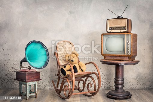 1065736660 istock photo Retro outdated television, broadcast radio from circa 50s on wooden table,  old phonograph, Teddy Bear toy sitting on aged rocking chair front concrete wall background. Vintage style filtered photo 1141305415