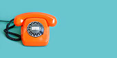 Retro phone orange color, vintage handset receiver on green background. copy space