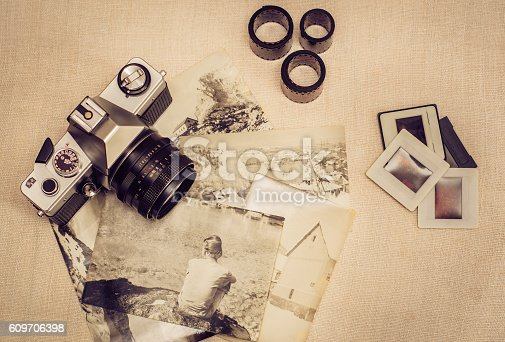609706398 istock photo Retro photo camera with old photographs, film rolls and slides 609706398