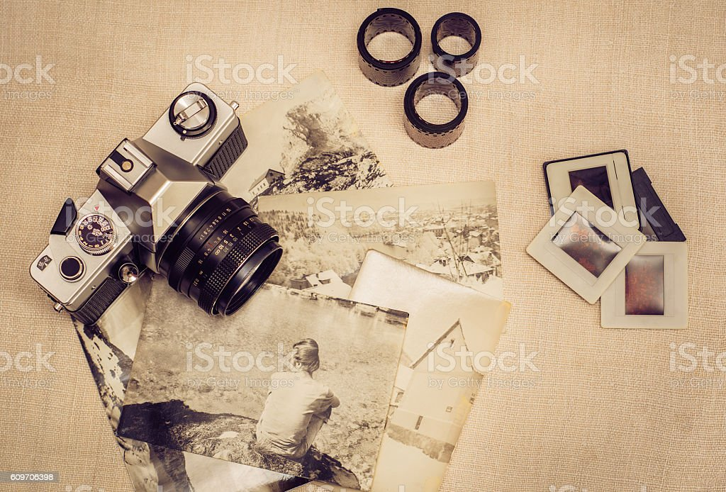 Retro photo camera with old photographs, film rolls and slides stock photo