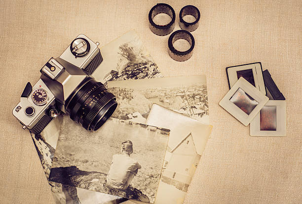 Retro photo camera with old photographs, film rolls and slides - Photo