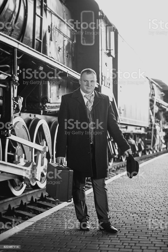 retro photo of man in suit waiting for train stock photo