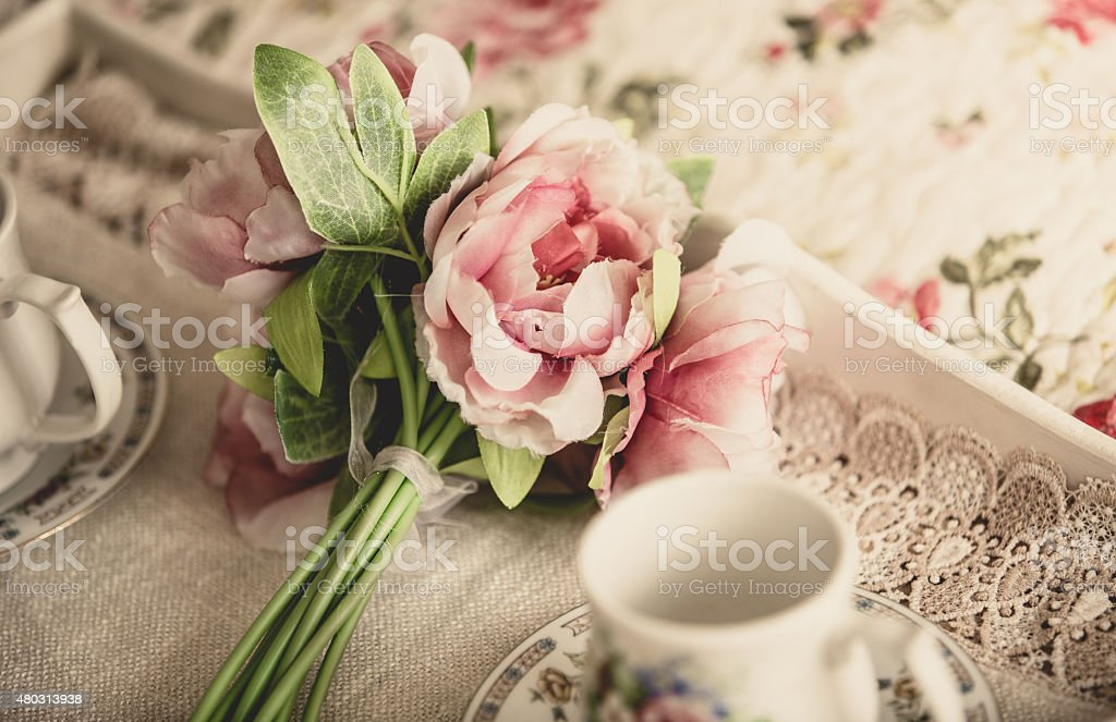 retro photo of pink flowers lying on tray with teacups stock photo
