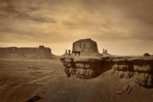 retro-foto von western cowboy indianer mit pferd in monument valley tribal park - navajo stil stock-fotos und bilder