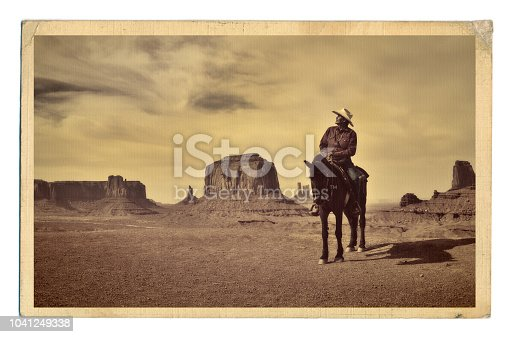 A retro style photo of a native American cowboy and his horse at the edge of a butte cliff at the Monument Valley Tribal Park in Arizona, USA. A famous tourist destination in the southwest USA. The iconic western landscape is a backdrop for many western movies. The native American is a Navajo tribe native. Photographed on location in sepia tone.