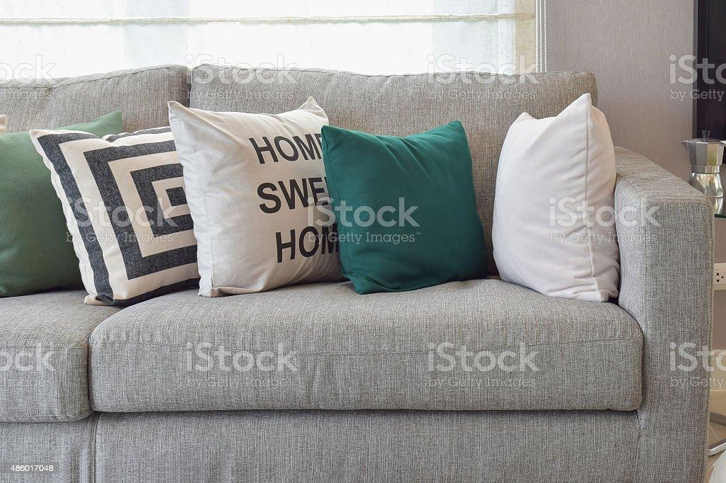 Retro pillows on the cozy grey sofa in living room stock photo