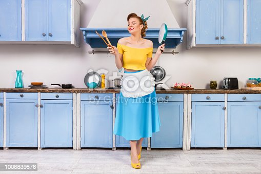 Retro pin up girl woman female housewife wearing colorful top, skirt and white apron and yellow high heels holding wooden spoons and pan standing in the blue kitchen with blue cabinets and utensils.