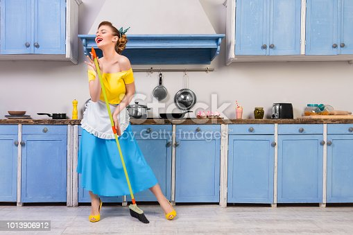 Retro / pin up girl woman female / housewife wearing colorful top, skirt and white apron holding mop singing and cleaning floor in the kitchen with blue cabinets and utensils. Housework concept
