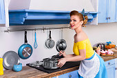 Retro pin up woman housewife in the kitchen