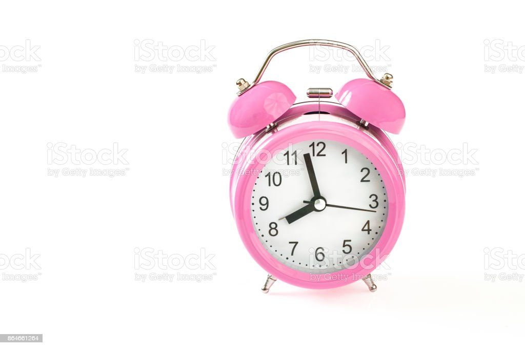 Retro pink alarm clock, with 2 minutes to 8 o'clock on it, Isolated on white background, Close up stock photo