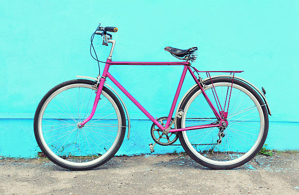 Retro pink bicycle stands over colorful blue background – Foto
