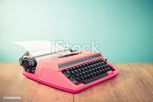 istock Retro pink typewriter with paper on wooden table front mint green background. Vintage old style filtered photo 1048998590