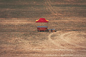 Retro pop corn stand, red and yellow, standing in the middle of nowhere in the big field, abandoned