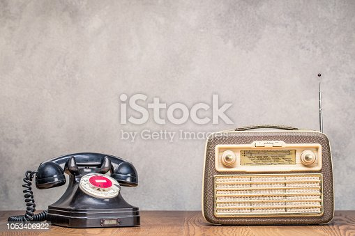 istock Retro portable broadcast radio receiver and black rotary telephone from circa 1950s on wooden table front textured concrete wall background. Listen music concept. Vintage old style filtered photo 1053406922