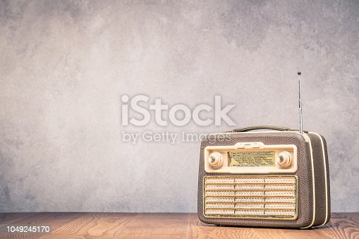 1065736660 istock photo Retro portable broadcast radio receiver with leather case design from circa 1950s on wooden table front textured concrete wall background. Listen music concept. Vintage old style filtered photo 1049245170