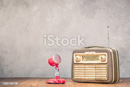 1065736660 istock photo Retro portable broadcast radio receiver with leather case design from circa 1950s and red microphone front textured concrete wall background. Listen music concept. Vintage old style filtered photo 1050193108