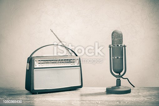1065736660 istock photo Retro portable broadcast radio receiver with leather case design from circa 1950s and studio microphone front textured concrete wall background. Listen music concept. Vintage old style sepia photo 1050365430