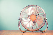 istock Retro portable office or home cooling fan in working mode standing on table. Vintage instagram style filtered photo 1049248894
