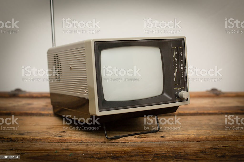 Retro Portable Television, Small Handheld TV, Vintage Electronics Color stock photo of a retro, vintage 1980s portable television unit with antenna, sitting on an old wooden trunk. 1980-1989 Stock Photo