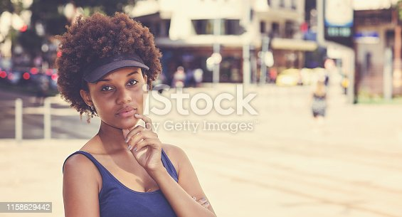 Retro portrait of a beautiful african american young adult woman outdoors in city in summer