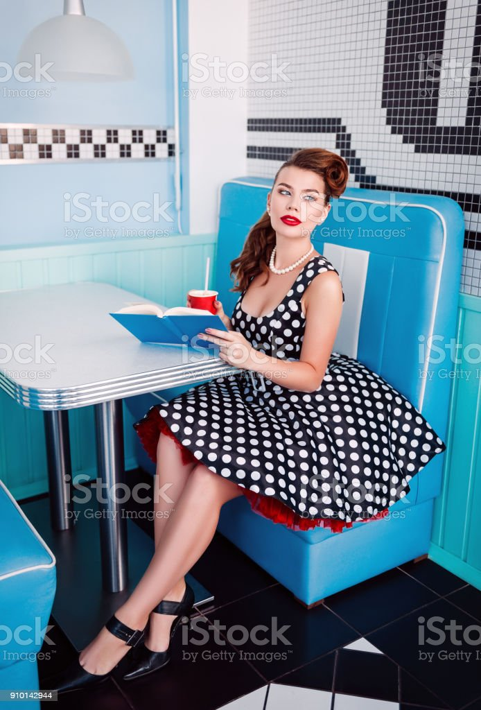 Retro (vintage) portrait of pretty young girl sitting in cafe with book and beverage. Pin up style portrait of young girl in dress stock photo