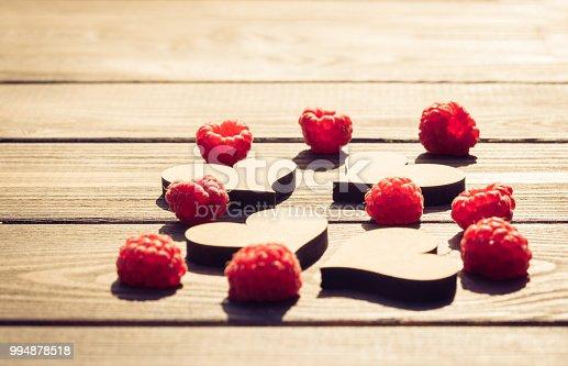 914465180istockphoto Retro postcard. Hearts and raspberries 994878518