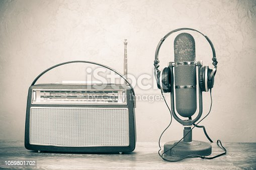 istock Retro radio and studio ribbon microphone from 50s with headphones on table. Vintage old style sepia photo 1059801702
