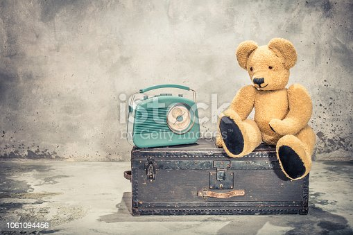 istock Retro radio and Teddy Bear toy sitting on old aged classic travel trunk with leather handles circa 1900s. Vintage instagram style filtered photo 1061094456