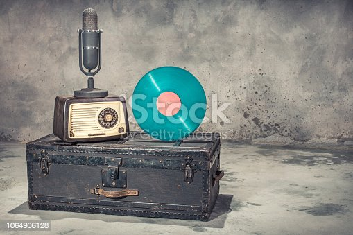 istock Retro radio from 60s, studio microphone from 50s, and blue vinyl disc record circa 70s on old aged classic travel trunk with leather handles. Vintage style filtered photo 1064906128