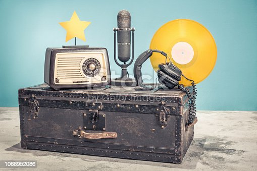 1065736660 istock photo Retro radio from 60s, studio microphone from 50s, and gold colored vinyl disc record circa 70s, headphones and star on old aged classic travel trunk with leather handles. Vintage style filtered photo 1066952086