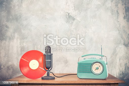 1065736660 istock photo Retro radio receiver, antique studio microphone and red color vinyl discs on wooden table front concrete wall background. Vintage old style filtered photo 1058795016
