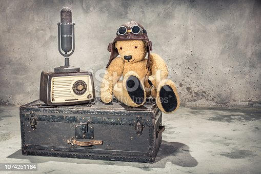 istock Retro radio, studio microphone, Teddy Bear toy with leather aviator's hat and goggles sitting on old aged classic travel trunk circa 1900s. Broadcasting concept. Vintage style filtered photo 1074251164