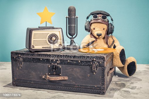 1065736660 istock photo Retro radio, studio microphone, vinyl disc and golden star on old aged classic travel trunk and DJ Teddy Bear toy with leather aviator's hat, headphones and goggles. Vintage style filtered photo 1065173374