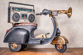 Retro radio with cassette tape recorder on old black toy scooter from circa 80s in front concrete textured wall background. Listening music concept. Vintage style filtered photo