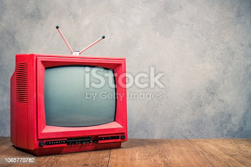 1056306726istockphoto Retro red outdated classic TV receiver on table front textured concrete wall background. Television broadcasting concept. Vintage old style filtered photo 1065770782