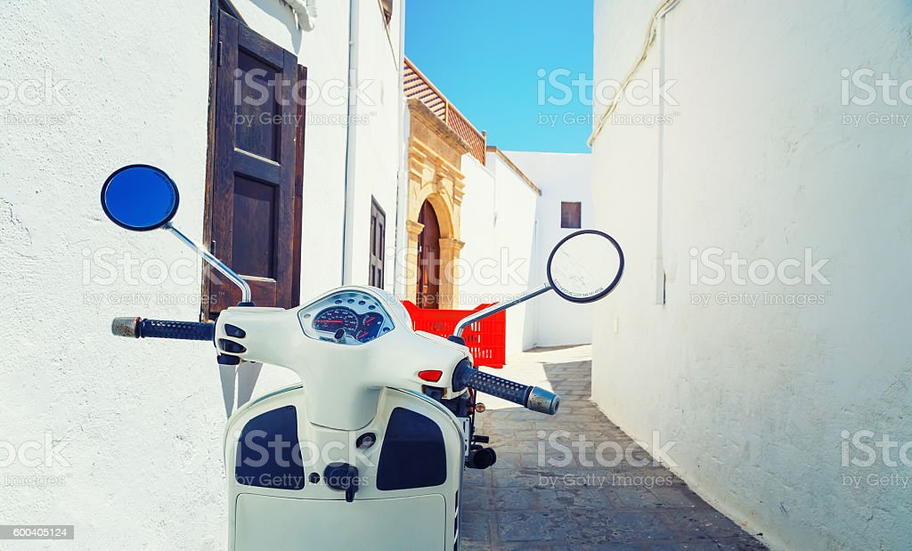 Retro red scooter old town narrow street. Vertical oriented photo. stock photo
