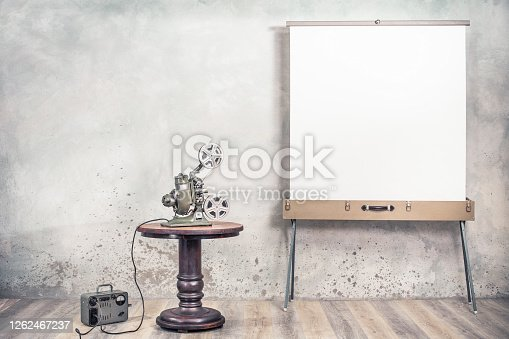 istock Retro reel movie projector from 1940s on round wooden table, outdated electrical energy transformer and portable screen for cinema. Silent movie concept. Vintage style filtered photo 1262467237
